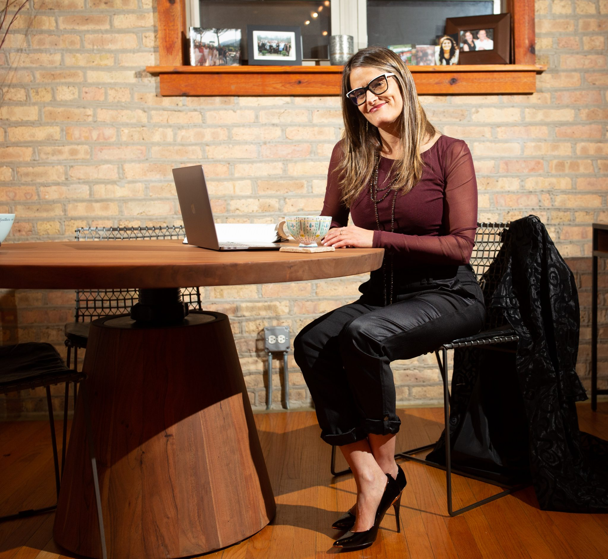 Woman sitting at table with glasses typing and smiling